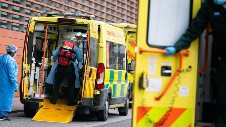 Paramedics transfer a patient from an ambulance into Royal London Hospital