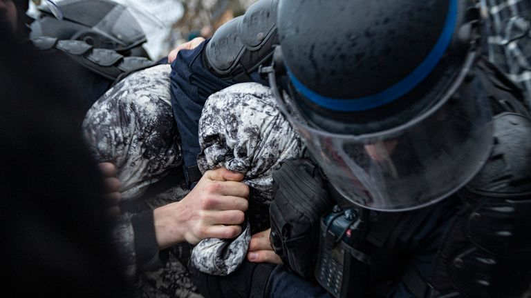 French riot police get a man in a headlock during protests in central Paris