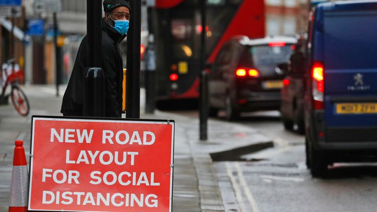 Pic: AP A man wearing a face mask waits beside a sign informing of a new road layout for social distancing, in London, Tuesday, Jan. 19, 2021. The U.K. is under an indefinite national lockdown to curb the spread of the new variant, with nonessential shops, gyms and hairdressers closed, most people working from home and schools offering remote learning. (AP Photo/Frank Augstein)