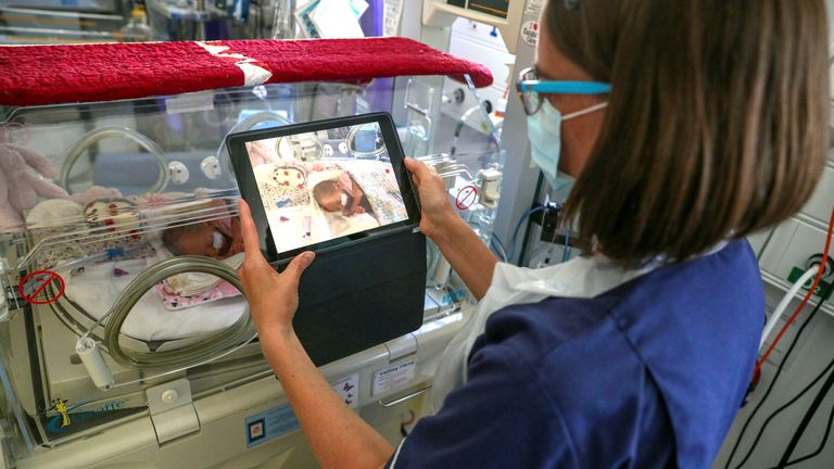 A nurse takes a video of a newborn baby in the maternity ward at Frimley Park Hospital in Surrey to send to the parents as visiting hours are restricted because of COVID-19 outbreak. May 27 2020