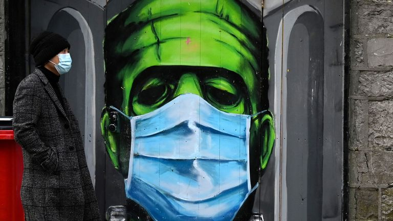 A man walks past a graffiti of a Frankenstein wearing a protective face mask on a doorway amid the spread of the coronavirus disease (COVID-19) pandemic, in Galway, Ireland, December 22, 2020. REUTERS/Clodagh Kilcoyne NO RESALES. NO ARCHIVES