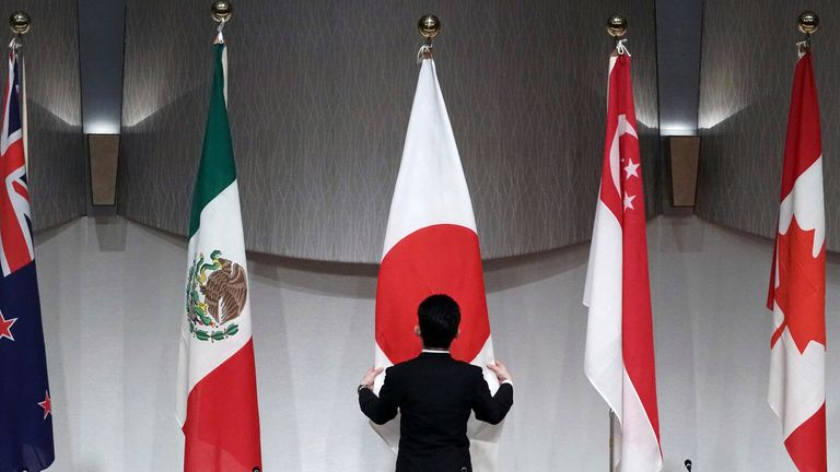The Japanese flag is adjusted ahead of a news conference held by the Comprehensive and Progressive Trans-Pacific Partnership (CPTPP)