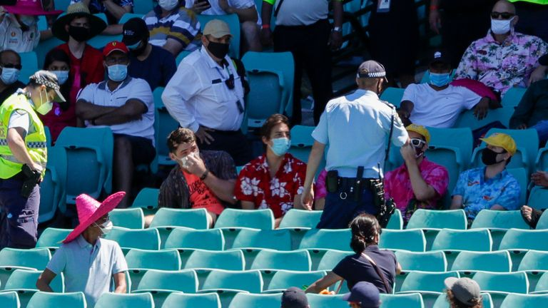 Police talk to spectators as the game is stopped after Indian players complained