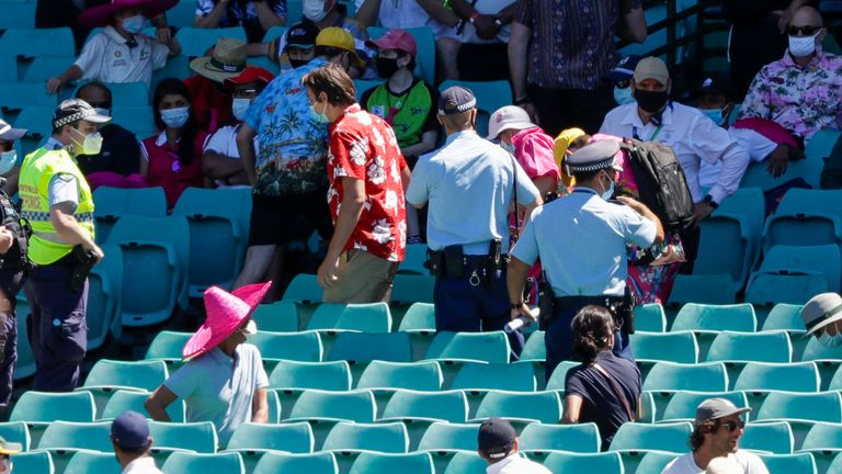 Police escort spectators from the stands during play on day four of the third test