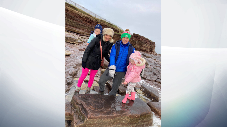 The Wilder family, pointing at the dinosaur footprint that Lily, far right, found