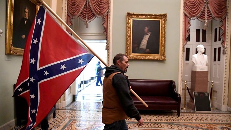 A supporter of Donald Trump carries a Confederate battle flag in the US Capitol