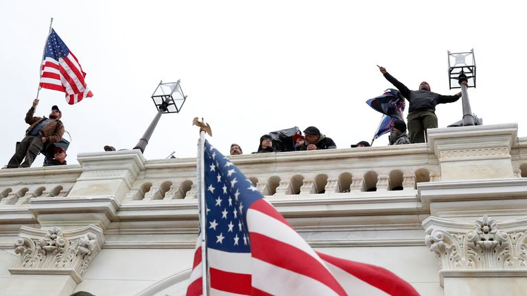 Pro-Trump protesters wave American flags after breaching the Capitol barricades