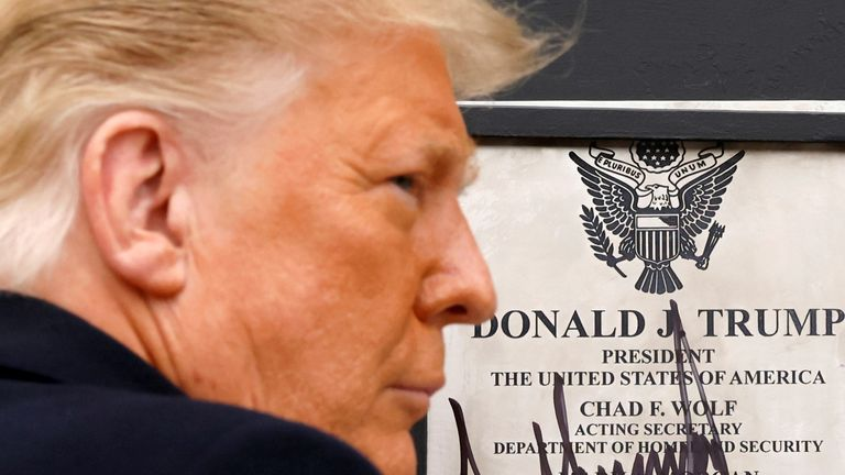 FILE PHOTO: U.S. President Donald Trump signs a plaque placed at the U.S.-Mexico border wall during his visit, in Alamo, Texas, U.S., January 12, 2021. REUTERS/Carlos Barria/File Photo