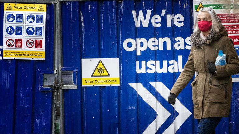 "A shopper walks past a sign that reads ""Virus Control Zone"" on a fence in Edinburgh"