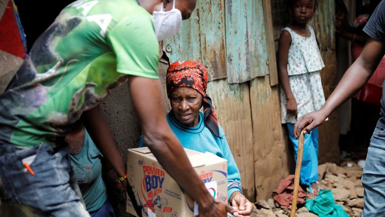 An elderly woman receives a box with food donations in Nairobi, Kenya