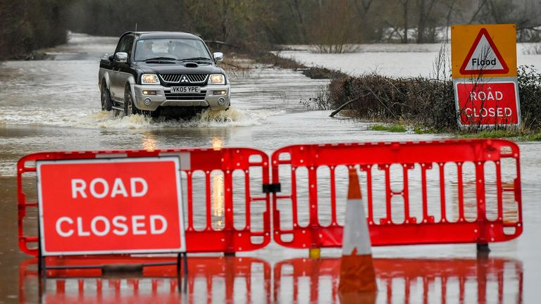 A 4x4 vehicle manages to drive through rising floodwater on the closed B1243 in Lower Applerlay, Gloucestershire