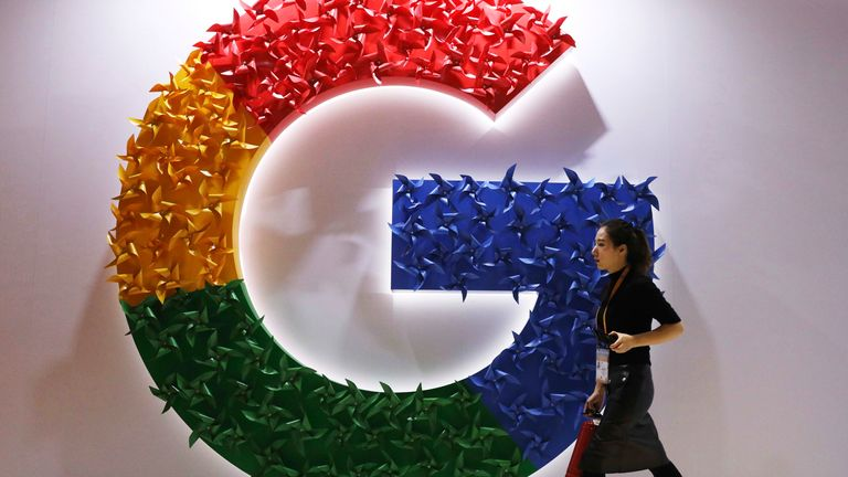 FILE - In this Monday, Nov. 5, 2018 file photo, a woman walks past the logo for Google at the China International Import Expo in Shanghai.  Chinese tech giant Huawei is racing to develop replacements for Google apps. U.S. sanctions imposed on security grounds block Huawei from using YouTube and other popular Google ...core apps.... (AP Photo/Ng Han Guan, FILE)