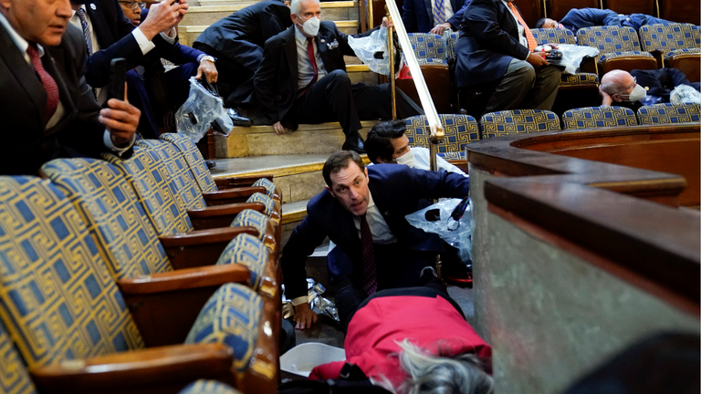 People shelter in the House gallery as protesters try to break into the House Chamber