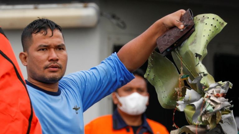 An Indonesian navy diver with some debris from the plane