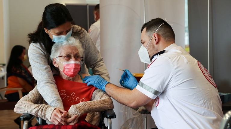 An elderly woman receives a booster shot in Israel