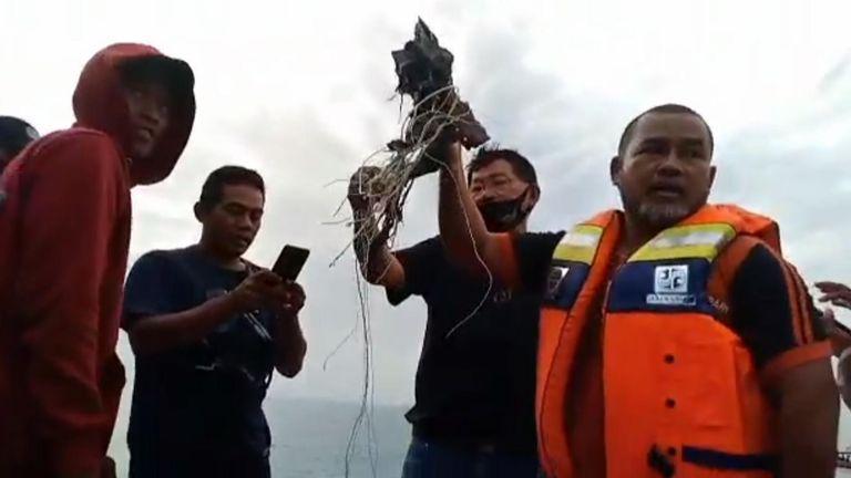 Fishermen held up metal objects in waters off Jakarta.