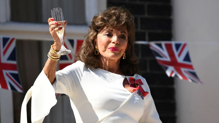 Actress Joan Collins on her balcony with a glass of champagne in London on the 75th Anniversary of VE Day, London in 2020