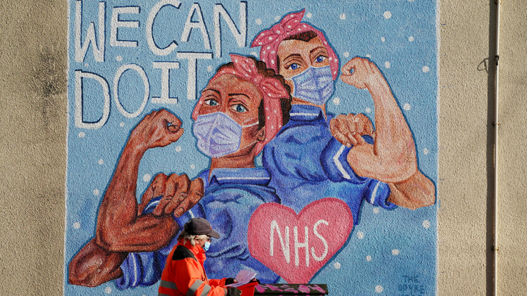 A Royal Mail delivery worker passes an NHS Mural in Loughborough, Leicestershire, during the third national lockdown.