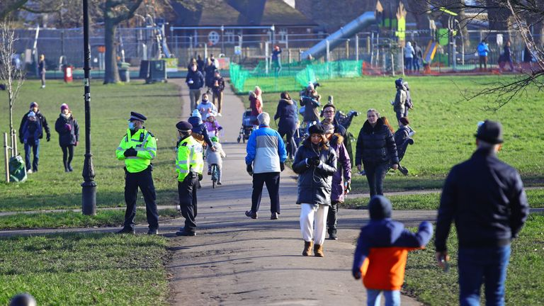 People walk on Clapham Common in London during England's third national lockdown to curb the spread of coronavirus. Under increased measures people can no longer leave their home without a reasonable excuse and schools must shut for most pupils.