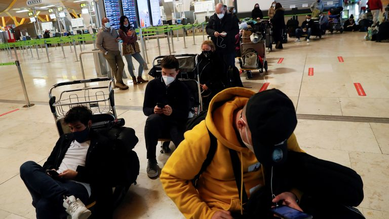 Stranded passengers wait for news about their flights at Adolfo Suarez Barajas airport