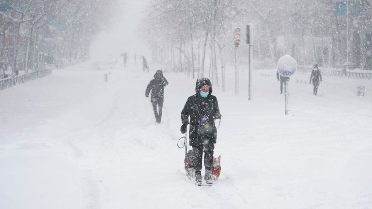 People walk and ski downtown during a heavy snowfall in Madrid