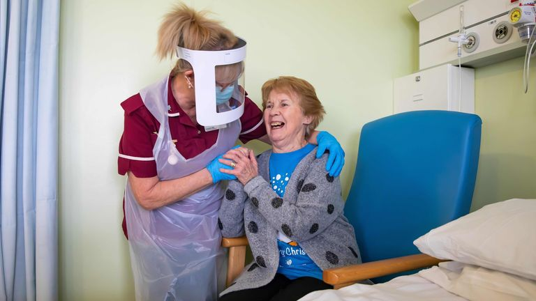 Margaret Keenan, 90, who was the first patient in the United Kingdom to receive the Pfizer-BioNtech Covid-19 vaccine, reacts as she talks with Healthcare assistant Lorraine Hill, while preparing to leave University Hospital Coventry, in Coventry on December 9, 2020, a day after receiving the vaccine. - Britain on December 8 hailed a turning point in the fight against the coronavirus pandemic, as it begins the biggest vaccination programme in the country's history