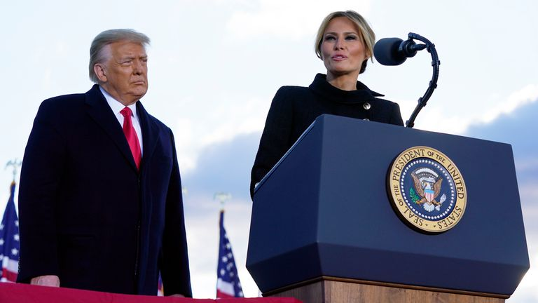 President Donald Trump listens as First Lady Melania Trump speaks before boarding Air Force One at Andrews Air Force Base. Pic: AP
