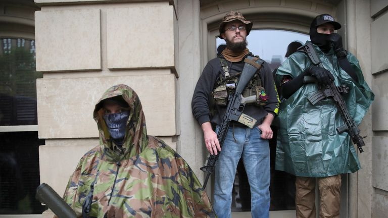 Protesters stand with their rifles during a rally at the State Capitol in Lansing, Mich., Thursday, May 14, 2020. (AP Photo/Paul Sancya)