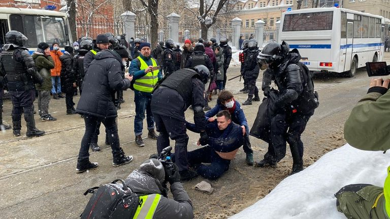 A man being detained by riot police