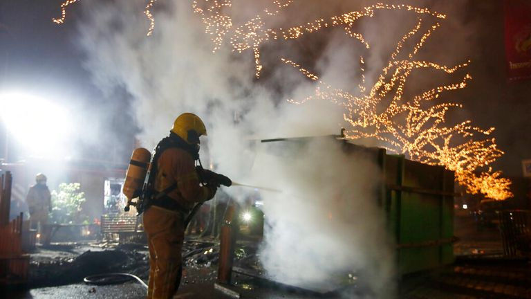 A firefighter extinguishes a container that was set alight during protests against a nation-wide curfew in Rotterdam, Netherlands, Monday, Jan. 25, 2021. Pic: AP
