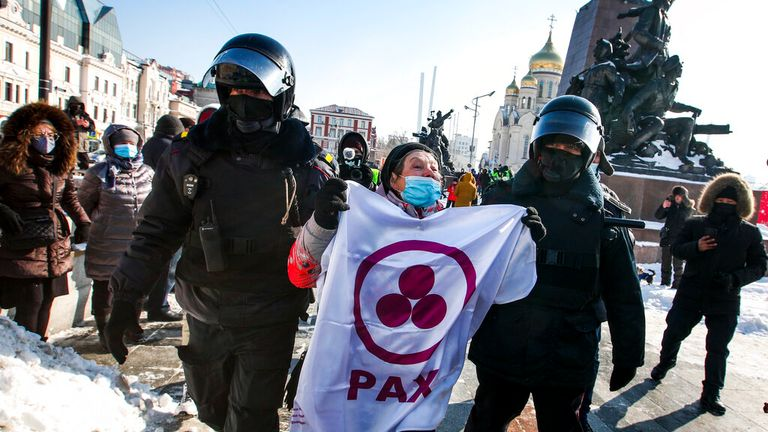 Police detain a woman during a protest against the jailing of opposition leader Alexei Navalny in Vladivostok, Russia. Pic: Associated Press