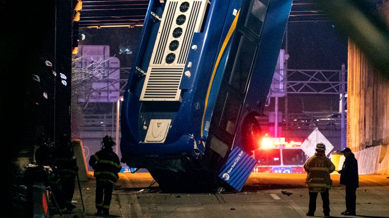 A bus in New York City careened off a road in the Bronx neighborhood of New York and was left dangling from an overpass Friday, Jan. 15, 2021, after a crash late Thursday that left the driver in serious condition, police said. (AP Photo/Craig Ruttle)