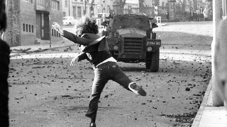 A teenager throws rocks at a British armoured car in the Catholic quarter of Londonderry in 1976