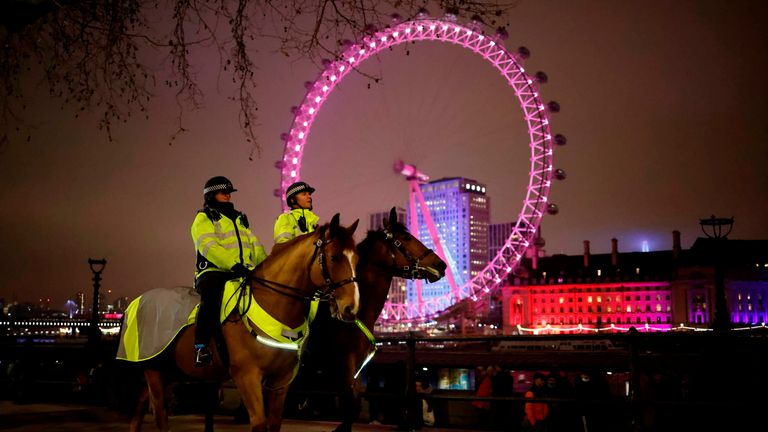 Officers patrol The Victoria Embankment opposite the London Eye in a near-deserted London