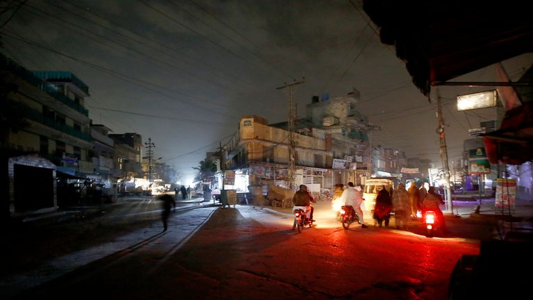 People are silhouetted on vehicles headlights on a dark street during widespread power outages in Rawalpindi, Pakistan
