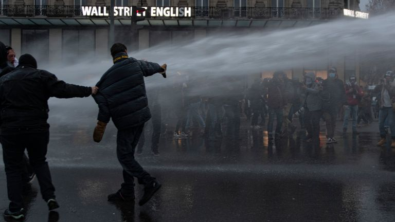 Water cannons were used to clear protesters ahead of a 6pm curfew. Pic: AP
