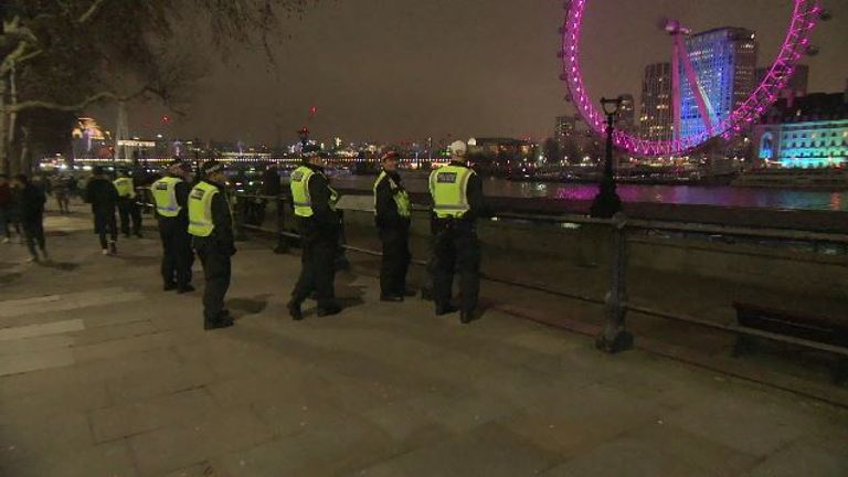 Police officers look over the River Thames on New Year's Eve