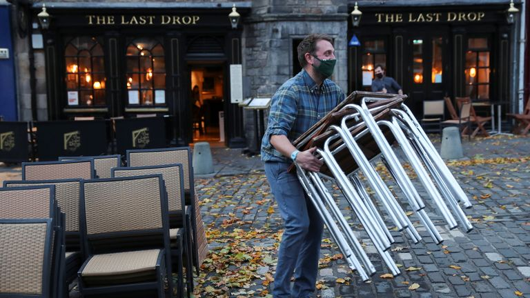 A worker carries tables as he prepares to close a pub at Grassmarket, amid the coronavirus disease (COVID-19) outbreak, in Edinburgh, Britain October 9, 2020. REUTERS/Russell Cheyne