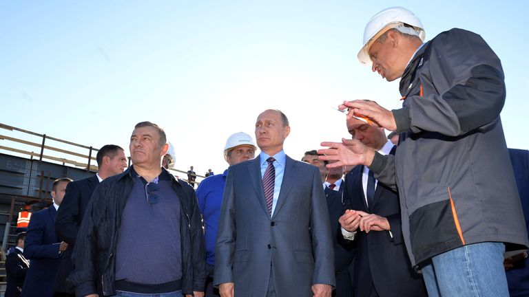 Russian President Vladimir Putin (C) and businessman Arkady Rotenberg (L) visits the site of the construction of a bridge across the Kerch Strait in Kerch, Crimea,