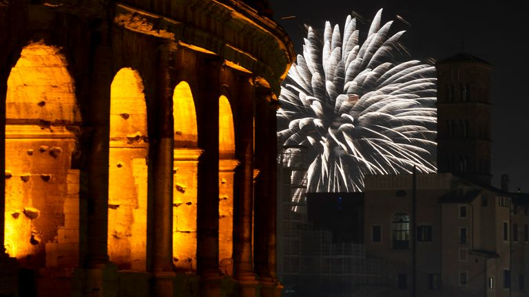 Fireworks explode in the sky next to Rome's Colosseum during New Year's celebrations