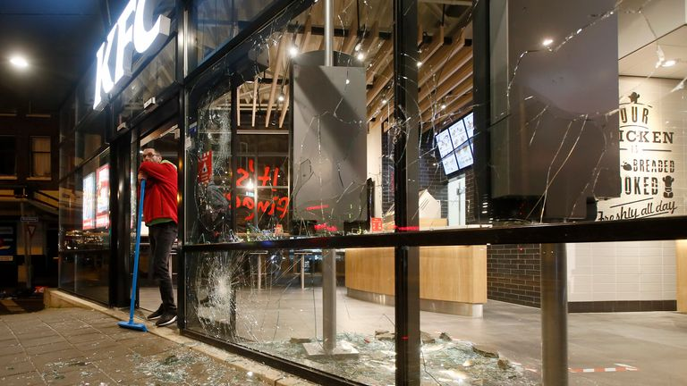 A man rests on his broom as he stands next to shards of glass and smashed windows of a fast-food restaurant that was damaged in protests against a nation-wide curfew in Rotterdam, Netherlands, Monday, Jan. 25, 2021. The Netherlands Saturday entered its toughest phase of anti-coronavirus restrictions to date, imposing a nationwide night-time curfew from 9 p.m. until 4:30 a.m. in a bid to control the COVID-19 infection rate. Pic: AP