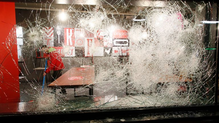 A man cleans up and is seen through the damaged glass in a fast-food restaurant that was smashed in protests against a nation-wide curfew in Rotterdam, Netherlands, Monday, Jan. 25, 2021. The Netherlands Saturday entered its toughest phase of anti-coronavirus restrictions to date, imposing a nationwide night-time curfew from 9 p.m. until 4:30 a.m. in a bid to control the COVID-19 infection rate. (Pic: AP)