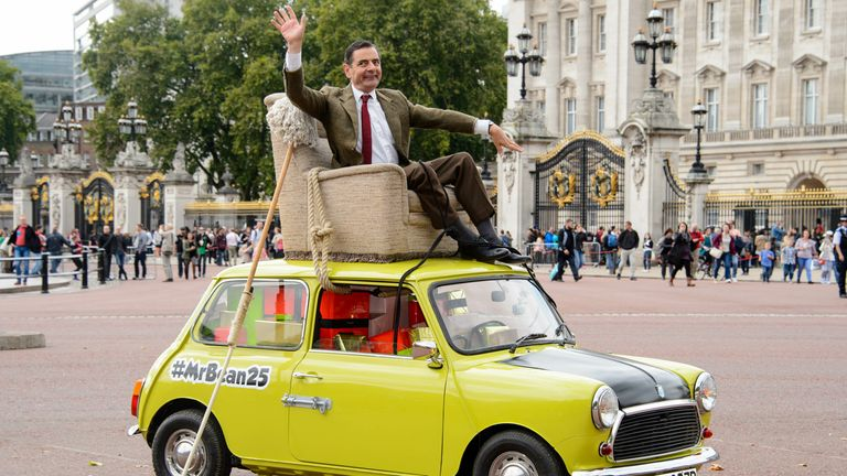 British actor Rowan Atkinson, dressed as Mr Bean, sits on top of a Mini Cooper outside Buckingham Palace, London, to promote the 25th anniversary of Mr Bean, London, Friday, Sept. 4, 2015. (Photo by Jonathan Short/Invision/AP)