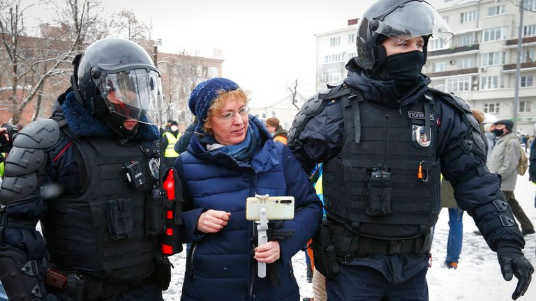 Police officers detain a woman during protests in Moscow