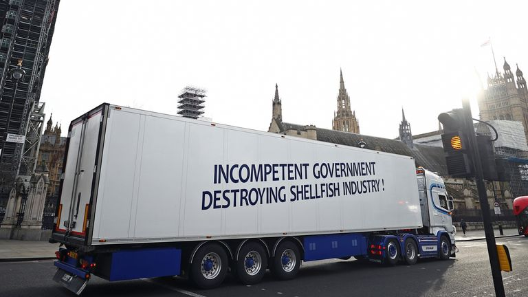 A lorry with a sign in protest against post-Brexit bureaucracy that hinders exports to the European Union, drives at the Parliament Square in London, Britain, 18 January 2021. REUTERS/Hannah McKay