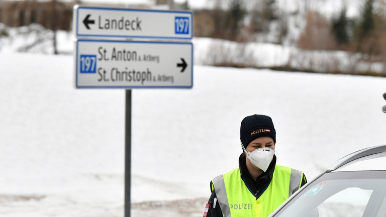 Police at a roadblock stop a cars from driving into and out of the village St. Anton, Austrian province of Tyrol, Saturday, March 14, 2020. Due to the Covid-19 virus, the towns of St. Anton am Arlberg and the Paznauntal area are isolated for 14 days. Only for most people, the new coronavirus causes only mild or moderate symptoms, such as fever and cough. For some, especially older adults and people with existing health problems, it can cause more severe illness, including pneumonia. (AP Photo/Ke