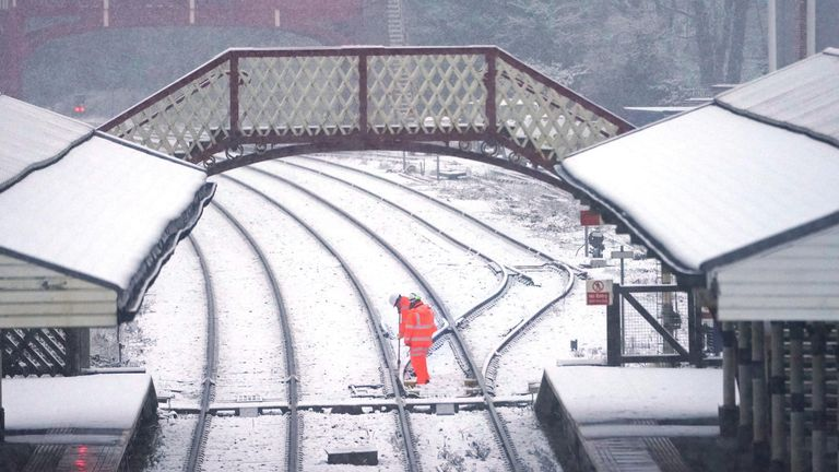 Rail workers checking the points at Hexham train station, Northumberland after overnight snow