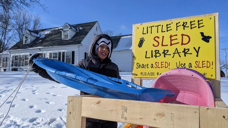Jace Prohaska, 9, of Kansas City, Missouri, borrows a sled from the Little Free Sled Library Monday morning in Ventura. He and his brother spent hours at the sledding hill this past weekend.