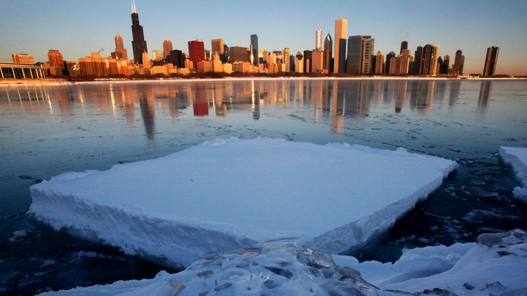 In this Feb. 3, 2011, file photo the Chicago skyline is reflected on a thin layer of ice as a chunk of snow-covered ice floats in Monroe Harbor one day after a blizzard dumped the third largest snowfall in Chicago's history. (AP Photo/Charles Rex Arbogast, File)