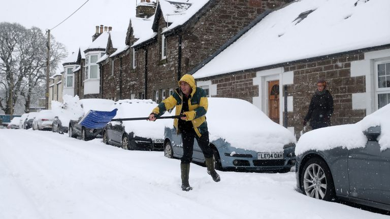 A man clears snow in Braco, near Dunblane in Scotland.